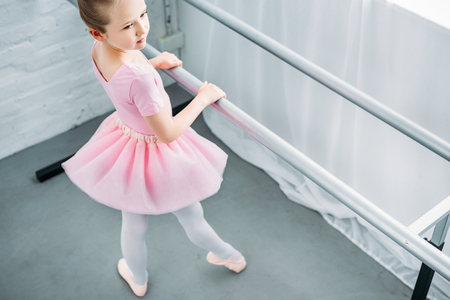 high angle view of graceful little ballerina exercising in ballet school