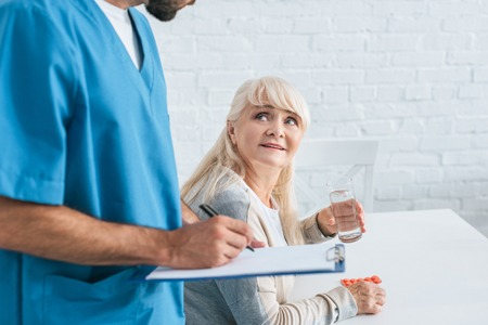cropped shot of caregiver writing on clipboard while senior woman holding glass of water and pills Stock Photo