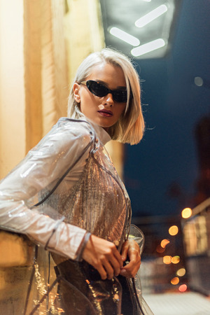 beautiful young woman in transparent raincoat and sunglasses looking at camera on street at night