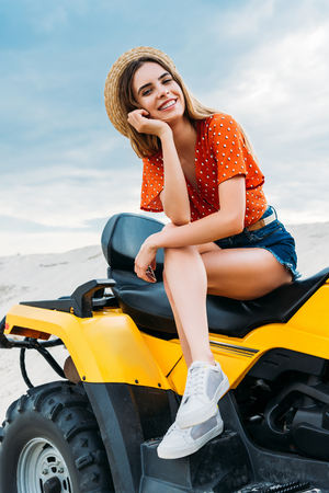 happy young woman sitting on all-terrain vehicle and looking at camera