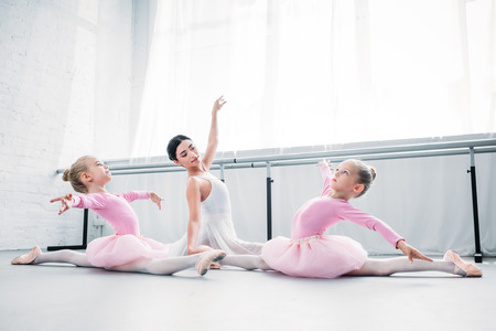 young ballet teacher training cute little ballerinas in ballet studio