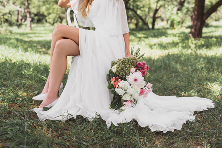 cropped shot of bride in wedding dress sitting on chair and holding bouquet of flowers outdoors