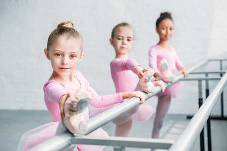 beautiful children looking at camera while stretching in ballet school Imagens