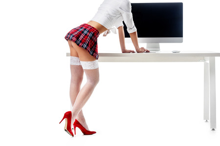 cropped shot of sexy schoolgirl in plaid skirt and stockings standing at table with blank computer screen isolated on white Фото со стока