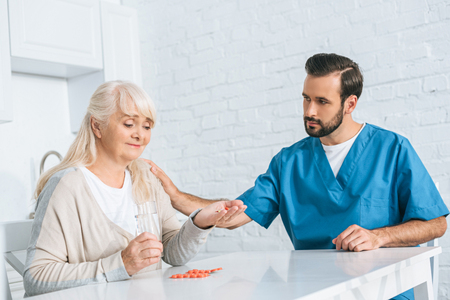 social worker looking at smiling senior woman taking medicine