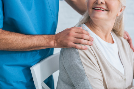 cropped shot of social worker supporting smiling senior woman Stock Photo