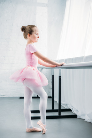 side view of adorable little ballerina in pink tutu exercising in ballet school