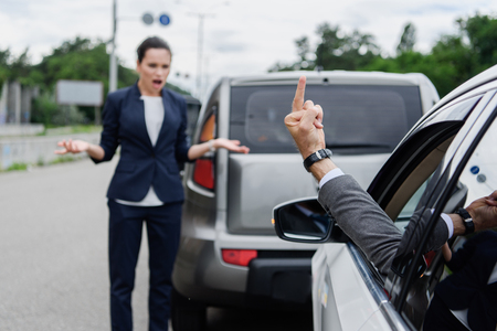 cropped image of driver showing middle finger to businesswoman on road