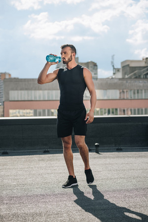 handsome sportsman drinking water after training on roof Banco de Imagens