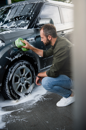 side view of handsome man cleaning car at car wash with rag