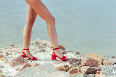 low section view of female legs in trendy red heeled sandals on rocky shore Stock Photo