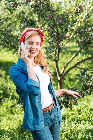 smiling attractive farmer talking by smartphone in apple garden at farm Stock fotó