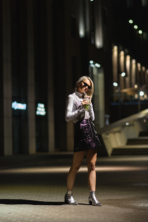 stylish young woman with mojito in plastic cup on dark street Stock Photo
