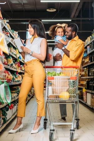 uśmiechnięty Afroamerykanin trzymający córkę, podczas gdy jego żona wybiera jedzenie z listy zakupów w supermarkecie