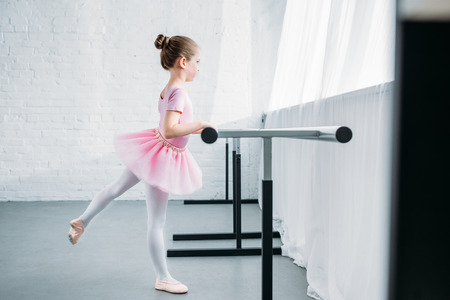 side view of child in pink tutu practicing ballet in studio