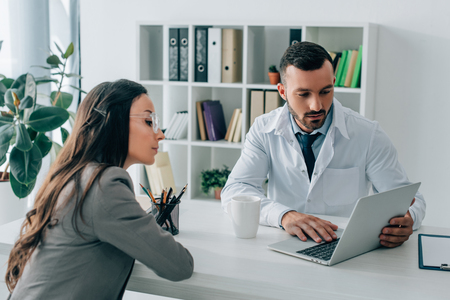 patient and general practitioner looking at laptop in clinic Stock Photo
