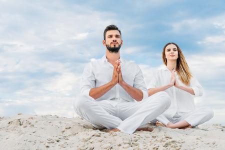 beautiful young couple practicing yoga while sitting on sandy dune in lotus pose (padmasana)