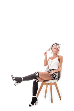 young blond woman in short plaid skirt and knee socks sitting on chair isolated on white Banque d'images - 109834656