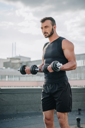 handsome sportsman training with dumbbells on roof Stok Fotoğraf