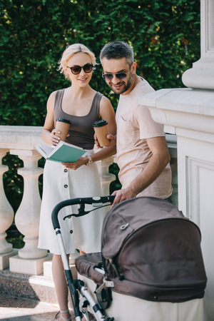 parents standing near baby carriage in park with book and coffee to go at looking at baby Banco de Imagens