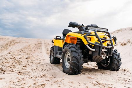 Unteransicht des modernen gelben Geländefahrzeugs, das in der Wüste am bewölkten Tag steht Standard-Bild