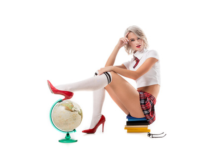 young sexy woman in schoolgirl uniform sitting on pile of books with leg on globe isolated on white 免版税图像