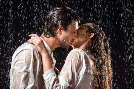 Seitenansicht des Paares, das unter Regen küsst, lokalisiert auf Schwarz