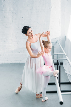 high angle view young ballet teacher exercising with adorable child in ballet studio Zdjęcie Seryjne