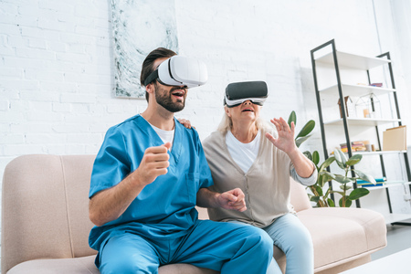 happy senior woman and young male nurse using virtual reality headsets 写真素材