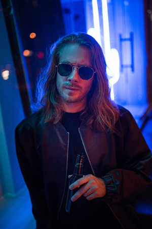 handsome young man in leather jacket and sunglasses with bottle of beer on street at night under blue light