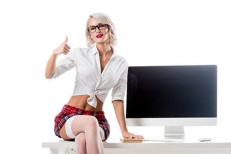 seductive schoolgirl in short plaid skirt showing thumb up while sitting on table with blank computer screen isolated on white Foto de archivo