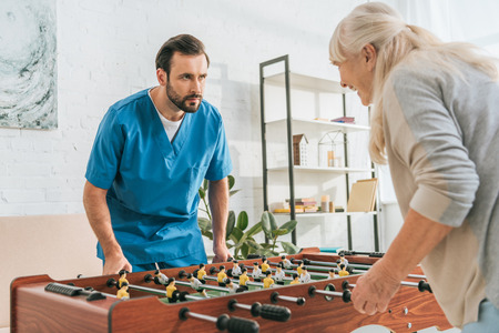 young male social worker playing table football with smiling senior woman