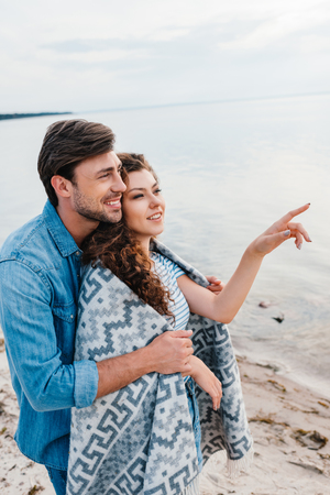 happy man hugging girlfriend wrapped in blanket while she pointing at sea Stock Photo