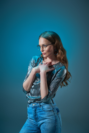 beautiful woman in stylish outfit and eyeglasses looking away isolated on blue Фото со стока