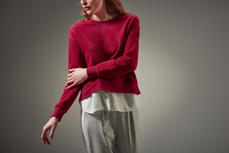 cropped shot of woman in red sweater and stylish pants posing isolated on grey 版權商用圖片