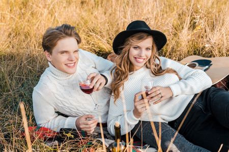 smiling couple holding wineglasses with red wine on meadow