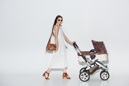 fashionable woman in white dress and sunglasses walking with baby carriage and looking at camera on grey