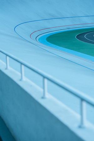 close-up view of white railing and empty velodrome, urban background