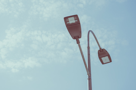 low angle view of street lamps against blue sky, toned image Stok Fotoğraf