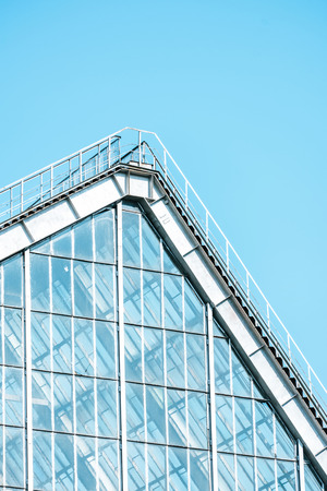 low angle view of glass building and roof against blue sky Stok Fotoğraf