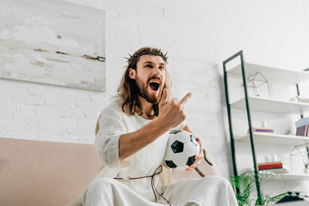 angry Jesus in crown of thorns showing middle finger during watching of soccer match at home