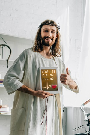 cheerful Jesus in crown of thorns doing thumb gesture and showing digital tablet with medical application at home