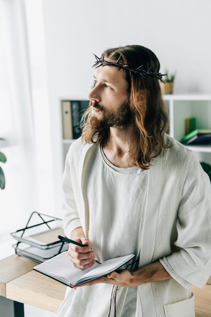pensive Jesus in crown of thorns and robe holding textbook and looking away in modern office Фото со стока