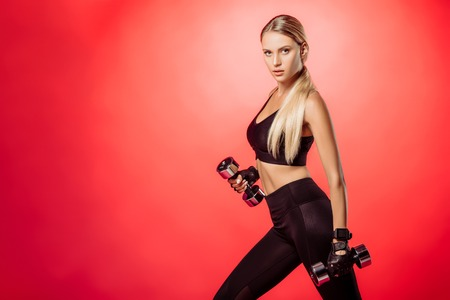 attractive sportswoman training with dumbbells isolated on red and looking at camera