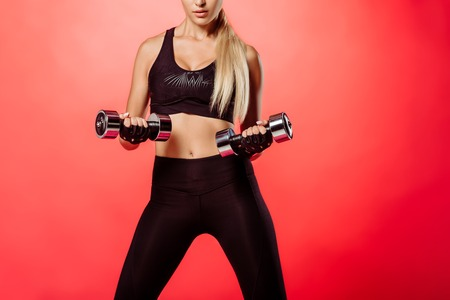 cropped image of sportswoman training with dumbbells isolated on red