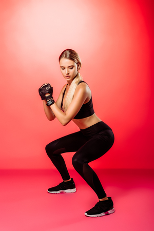 attractive sportswoman training and doing squats on red