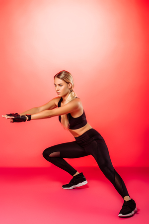 attractive sportswoman training and doing squats on one leg on red