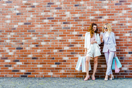 beautiful young women with shopping bags using smartphone while standing in front of brick wall Stock Photo