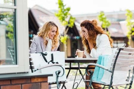 happy young women sitting in cafe together after shopping