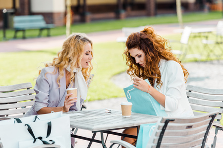 stylish young women checking buys while sitting in cafe after shopping